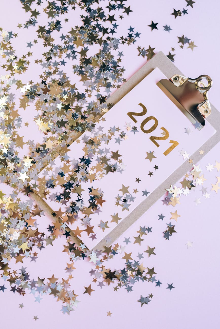 A clipboard with a planner for the year 2021 and shiny stars sprinkled around like confetti.