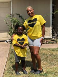 One young Black woman and one younger black girl standing close together wearing matching yellow t-shirts with the black sparkly hearts that say Melanin. There is a cream house in the background.