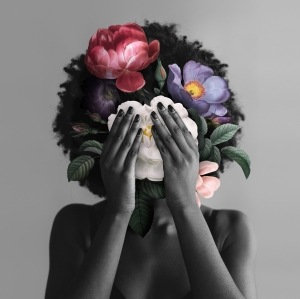 Black woman with Afro hiding her face with flowers.