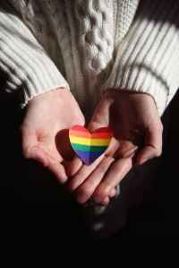 A pair of hands holding a rainbow paper heart