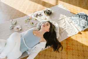 Anglo woman lying on yoga blanket with her eyes closes