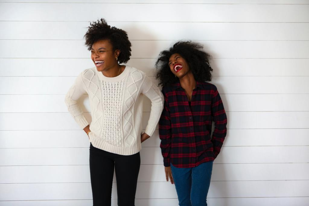 Two Black women laughing together in front of a white background.
